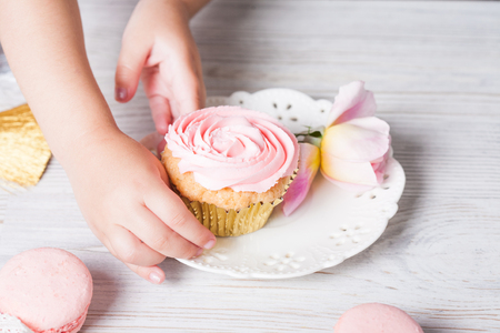 Cute little girl holding birthday cupcakes in kitchen. Festive and holiday concept Stock Photo
