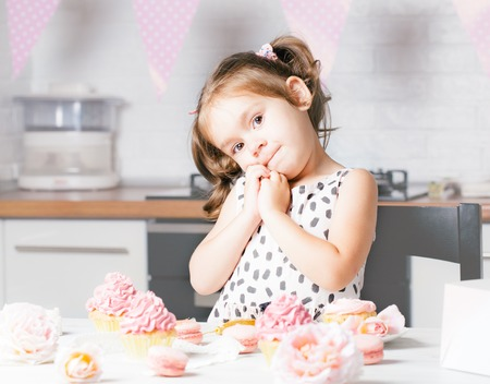 Cute little girl and birthday cupcakes in kitchen. Festive and holiday concept