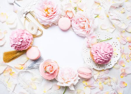 Pink cupcakes with roses and holiday decor in frame. Festive and bright. Wedding Celebration concept. Copy space.