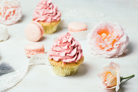 Pink cupcakes with roses and macaroons. Festive and bright. Wedding Celebration concept.
