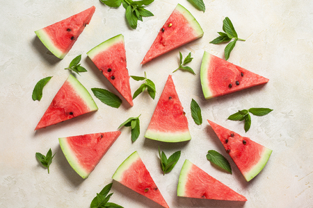 watermelon slices with mint leaves on white concrete background. Fresh summer concept. Top view, flat lay. Stock Photo