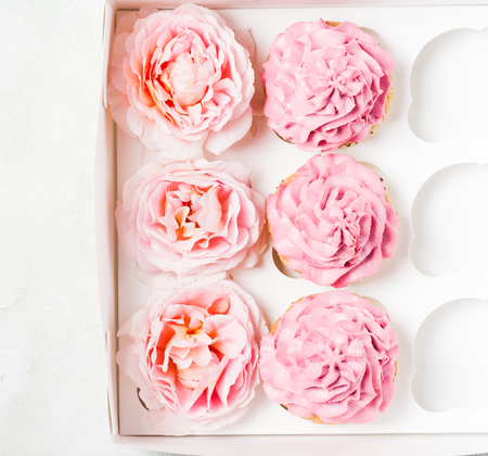 Pink cupcakes with roses in box. Festive and bright. Wedding Celebration concept. top view, flat lat