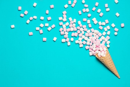 青の背景にワッフル コーンでピンクと白のマシュマロ。トップ ビュー フラット横たわっていた。テキストの無料スペース 写真素材