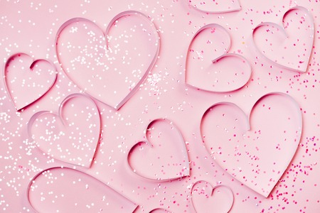 Pink hearts and sparkles on pink background. St. Valentines greeting concept, romantic style. Top view, flat lay Stock Photo