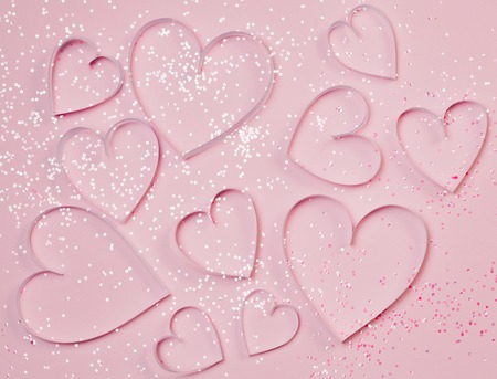 Pink hearts and sparkles on pink background. St. Valentines greeting concept, romantic style. Top view, flat lay.