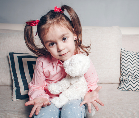 Pretty happy little girl in casual wearing sitting on sofa with toy dog and smiling.
