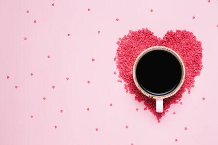ピンクの背景にブラックコーヒーとピンクのハートのカップ。バレンタインデーのコンセプト、女性の日。トップビュー, フラットレイ