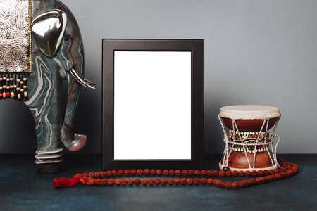 Mock up frame and statuette of elephant and Shivas drum Damar with rudraksha beads. Ethnic Shiwais picture.