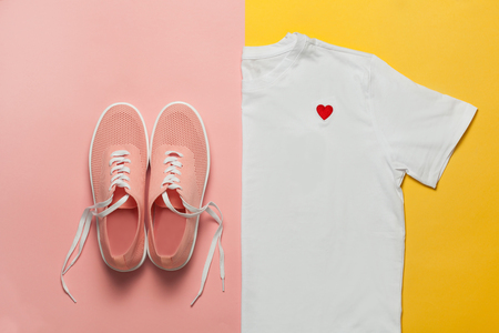 Top view of white woman t-shirt and pink shoes on pink and yellow background. Fashion clothes set. Flat lay. Place for text. 90's style.