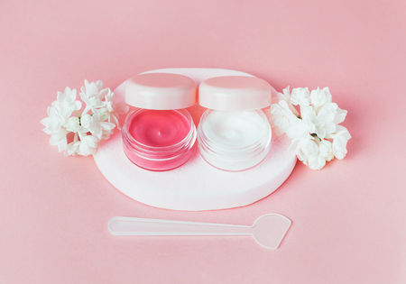 Close up of decorative cosmetic and creams with white lilac flowers on pink background. Beautiful cosmetic set. copyspace.