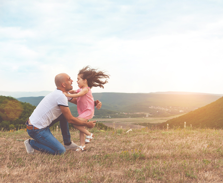 Father holds his pretty daughter and they are huging on summer sunset. Lovely emotions, happy family concept Stock Photo