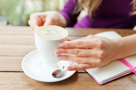 Womans Hands writting at notebook in cafe. Bloggers life