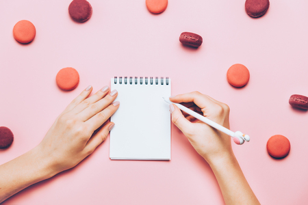 Female hands with trendy manicure writing in empty note book on pink background with many macaroons.