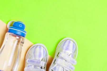 Baskets enfant et bouteille d'eau sur fond vert. Vue de dessus, mise à plat. Copyspace pour le texte. Concept de mode de vie sain pour les enfants. Banque d'images