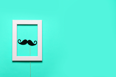 paper mustache and a notepad on blue background. November concept, flat lay, top view, copyspace for text. Stock Photo