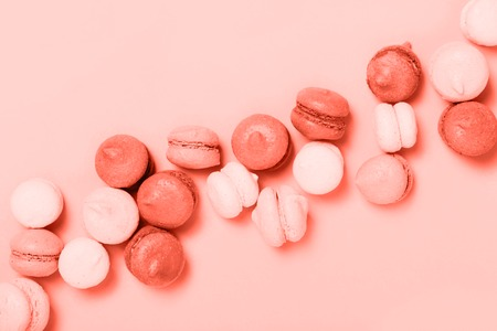 Group of sweet mini macarons colored in Living Coral trendy color. Creative concept of color of the year 2019. Top view, flat lay.