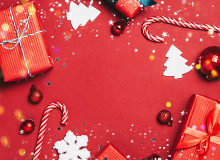 Red christmas Background with holiday decorations, fir brances, christmas candies and Merry Christmas text.