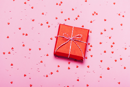 Pink holiday background with present gift box and little hearts on background.
