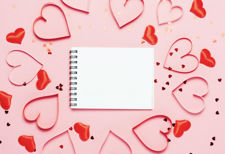 Valentine's day background. Little red hearts on pink background and empty notepad..