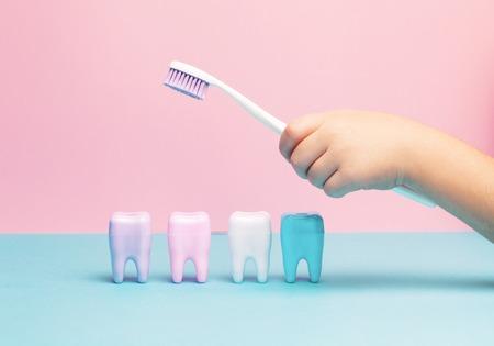 Kinderhände, die großen Zahn und Zahnbürste auf rosafarbenem Hintergrund halten. Konzept für gesunde Zähne. Ansicht von oben, flach. Kopieren Sie Platz für Ihren Text. Standard-Bild