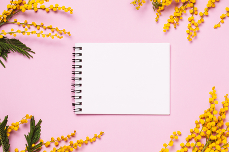 Spring yellow flowers and empty notepad on trendy background. top view, flat lay. Copyspace for text. 80s or 90s neon color style