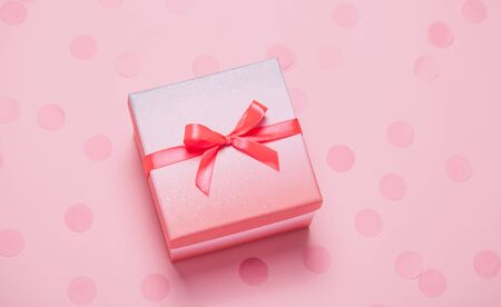 Pink present box on pink konfetti background. Banque d'images - 127123107