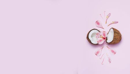 Broken coconut with tropic flowers on pink background. Banque d'images - 127123121
