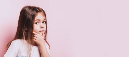 Funny portrait of little doubt girl on pink background. Banque d'images - 127123123