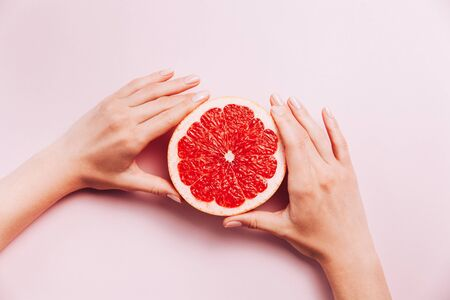 Females hands holding grapefruit on pink background with tropic plants and leaves. Banque d'images - 127059562