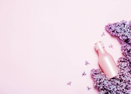 Creative minimal beauty and health background with pink bottle and lilac flowers. Minimal top view and flat lay of cosmetic on pink and blue trendy background. Banque d'images - 127167309