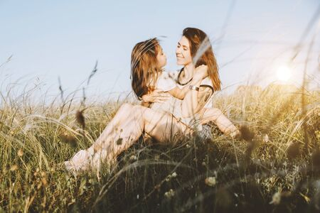 Happy mother and daughter hugging in summer field on sunset. Happy family concept. Girl power.