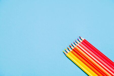 Colorful pencils on blue background. Copyspace.