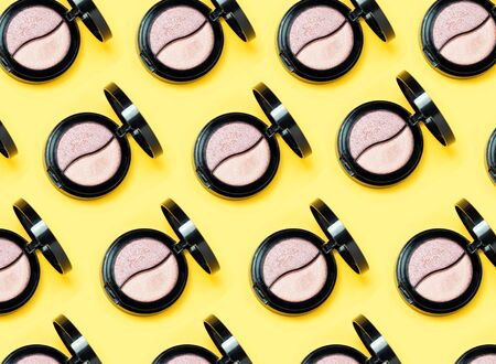 Three Eye shadows pallets and various make up brushes on yellow background.