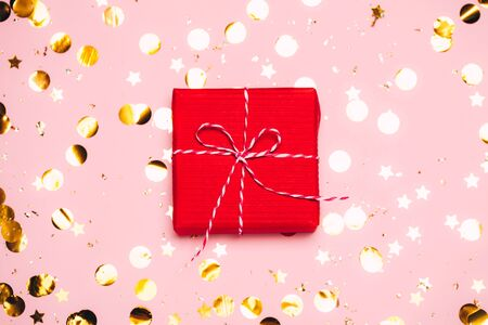 Christmas background with purple decorations and gift present box put as frame on pink background. Magic bokeh lights. Bright and festive flat lay. Top view, Greetings for christmas or new year.