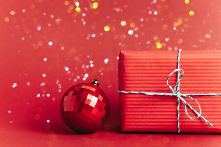 Christmas red background with christmas balls and present with candies and snow falling on them. Christmas festive flat lay concept. Copy space for text. 写真素材 - 132835970