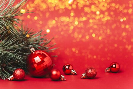 Christmas red background with christmas balls and present with candies and snow falling on them. Christmas festive flat lay concept. Copy space for text.