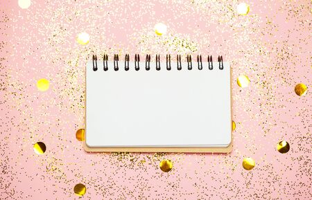 Empty note pad on pink confetti background. Top view, flat lay. Holiday and festive Christmas mock up.