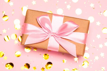 Christmas background with purple balls and present gift box and decoration on pink background.