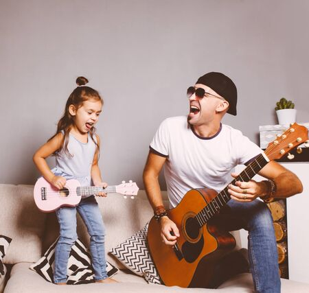 Beautiful little girl playing guitar with her father.