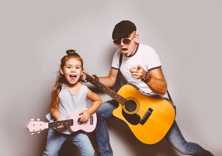 Beautiful little girl playing guitar with her father. 写真素材 - 134737885