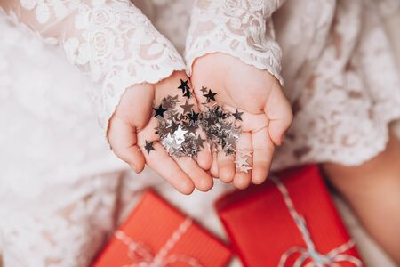 Silver stars sparkling on childs hands and palms. 写真素材 - 134737912