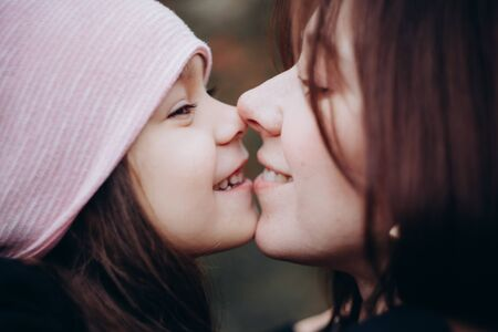 Beautiful mother and daughter hugging in autumn forest. 写真素材