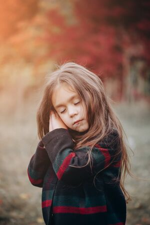 Portrait of cute little girl in autumn forest.