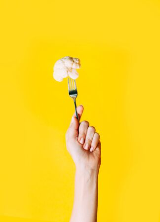 Female hand holding fork and cauliflower on it on yellow background. Minimal concept of healthy eating and vegan.