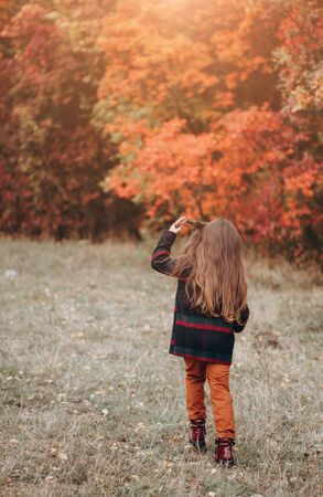 Cute little girl walking in autumn forest 写真素材 - 134737983