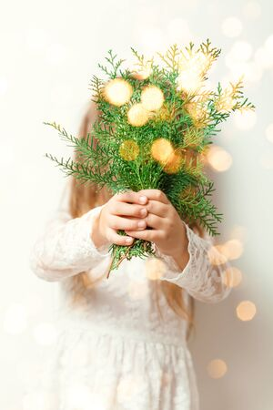 Cute happy little girl Laughing in Christmas atmosphere with gift boxes and magic lights. Happy child holding her Christmas present.