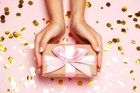 Female hands holding gift present box on festive confetti background. Top view, flat lay. Christmas greeting card. 写真素材 - 134738063