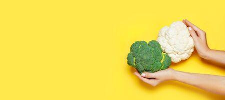 Female hand holding broccoli on yelow background. Minimal vegan concept. Healthy eating. 写真素材