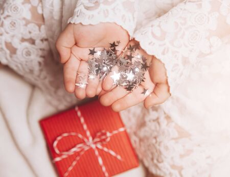 Silver stars sparkling on child's hands and palms. Christmas mood, cozy view. Bright and festive. 写真素材 - 134738079
