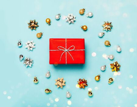 Minimalistic Christmas gift boxes wrapped in red paperon blue frozen background. Bright and festive Christmas concept. Top view, flat lay. Copy spce for text.